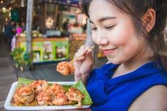 Muchacha linda de feliz asiático de comer a Mini Fried Mussels Imagen de archivo libre de regalías