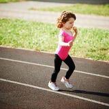 Muchacha linda de Ittle que corre en el estadio Foto de archivo