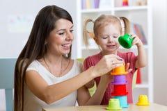 Muchacha linda de la mujer y del niño que juega los juguetes educativos en casa Foto de archivo libre de regalías