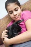 Muchacha linda de la raza mixta que sostiene un conejo del animal doméstico Foto de archivo libre de regalías