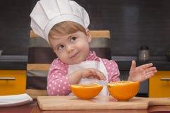 Muchacha linda de la sonrisa del retrato de Clouse-up pequeña en traje del cocinero Mother& x27; ayudante de s De 2 años Fotografía de archivo libre de regalías