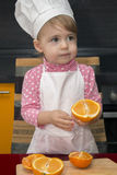 Muchacha linda de la sonrisa del retrato de Clouse-up pequeña en traje del cocinero Mother& x27; ayudante de s De 2 años Imagen de archivo libre de regalías