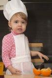 Muchacha linda de la sonrisa del retrato de Clouse-up pequeña en traje del cocinero Mother& x27; ayudante de s De 2 años Imagenes de archivo