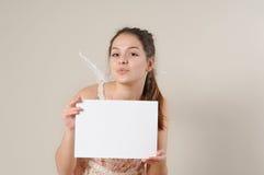 Muchacha linda del ángel que sopla un beso y que lleva a cabo un cartel en blanco Fotografía de archivo libre de regalías