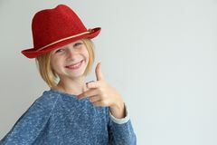 Muchacha linda del adolescente con el sombrero rojo en el fondo blanco Imágenes de archivo libres de regalías