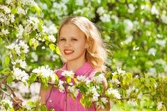 Muchacha linda del adolescente con las flores blancas en el peral Foto de archivo