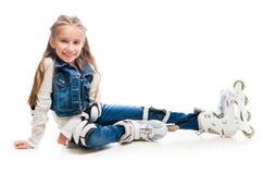 Muchacha linda del adolescente en sentarse de los rollerskates Foto de archivo libre de regalías