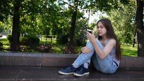 Muchacha linda del adolescente que comprueba el teléfono y que espera la llamada de teléfono que se sienta en parque Imágenes de  almacen de video