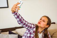 Muchacha linda del adolescente que hace el selfie en un smartphone Imágenes de archivo libres de regalías