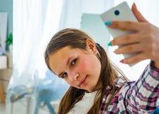 Muchacha linda del adolescente que hace el selfie en un smartphone Foto de archivo