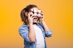 Muchacha linda del adolescente que juega con dos anillos de espuma en estudio Fotografía de archivo