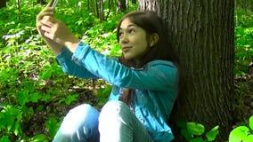Muchacha linda del adolescente que se sienta debajo de árbol en el parque y que hace selfies en smartphone Película de la cámara  metrajes