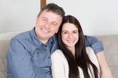 Muchacha linda del adolescente que se sienta en hogar del sofá con el padre Foto de archivo