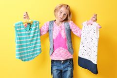 Muchacha linda del adolescente que sostiene suspensiones con ropa en fondo amarillo Fotos de archivo