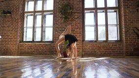 Muchacha linda del ajuste que hace calentando estirar en un gimnasio Aptitud del deporte gimnasia de la yoga entrenamiento del ej almacen de metraje de vídeo