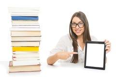 Muchacha linda del estudiante con los vidrios que muestran la pantalla en blanco de la tableta Fotos de archivo libres de regalías
