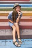 Muchacha linda del inconformista que se sienta en pasos coloridos en la calle Imagen de archivo