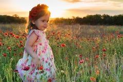 Muchacha linda del niño con la guirnalda de la flor en campo de la amapola Fotos de archivo