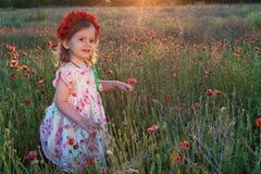 Muchacha linda del niño con la guirnalda de la flor en campo de la amapola Fotos de archivo libres de regalías