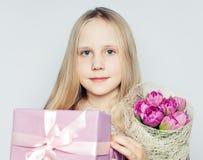 Muchacha linda del niño con las flores y la caja de regalo rosadas Foto de archivo libre de regalías