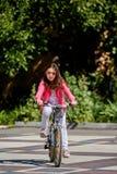 Muchacha linda del niño en el casco azul que va a montar su bici Foto de archivo libre de regalías
