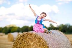 Muchacha linda del niño en traje bávaro tradicional en campo de trigo Niño alemán con la bala de heno durante Oktoberfest adentro imagen de archivo