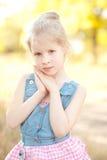 Muchacha linda del niño que presenta en fondo de la naturaleza Imagen de archivo libre de regalías