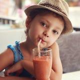 Muchacha linda del niño de la diversión que bebe el jugo sano del smoothie en resto de la calle Foto de archivo