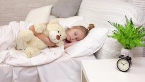 Muchacha linda del peque?o ni?o que duerme con el oso de peluche almacen de video