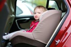 Muchacha linda del preescolar que se sienta en el coche Imagenes de archivo