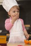 Muchacha linda del retrato de Clouse-up pequeña en traje del cocinero Mother& x27; ayudante de s De 2 años Imágenes de archivo libres de regalías