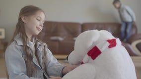 Muchacha linda del retrato que juega con un oso septentrional del juguete, vistiéndolo una corona y su hermano gemelo que saltan  almacen de video