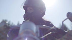 Muchacha linda del retrato que lleva el casco negro que se sienta en la motocicleta que mira lejos Afición, el viajar y forma de  almacen de metraje de vídeo