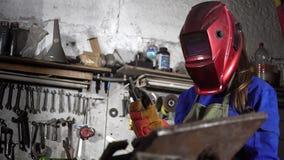 Muchacha linda del soldador en uniforme en el garaje que trabaja con el equipo de soldadura Trabajo del ` s de las mujeres en art almacen de metraje de vídeo