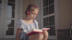 Muchacha linda durante las vacaciones de verano que se sientan en el patio cerca de casa que escucha la música, cantando y libro  almacen de video