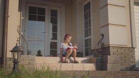 Muchacha linda durante las vacaciones de verano que se sientan en el patio cerca de casa que escucha la música, cantando y libro  metrajes