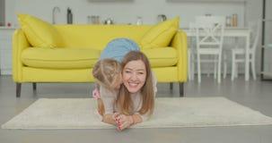 Muchacha linda emocionada que lleva a cuestas a la mamá en el piso almacen de video