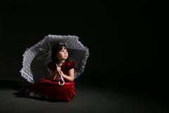 Muchacha linda en alineada roja con el parasol blanco Imagenes de archivo