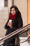 Muchacha linda en auriculares con la taza de café Imagen de archivo libre de regalías