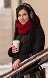 Muchacha linda en auriculares con la taza de café Imagen de archivo