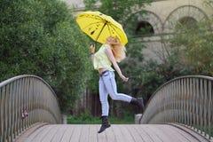 Muchacha linda en camisa amarilla y vaqueros que caminan en el puente con un paraguas brillante en la tarde fotografía de archivo