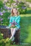 Muchacha linda en chaquetas azules con la falda airosa de hadas que se coloca cerca de arbusto de lila Imagenes de archivo