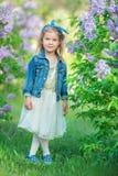 Muchacha linda en chaquetas azules con la falda airosa de hadas que se coloca cerca de arbusto de lila Foto de archivo