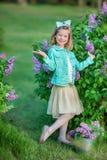 Muchacha linda en chaquetas azules con la falda airosa de hadas que se coloca cerca de arbusto de lila Fotos de archivo libres de regalías