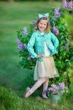 Muchacha linda en chaquetas azules con la falda airosa de hadas que se coloca cerca de arbusto de lila Imagen de archivo