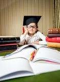 Muchacha linda en el casquillo de la graduación que se sienta en la tabla y que hace la preparación Imagen de archivo libre de regalías