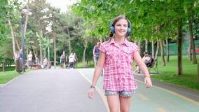 Muchacha linda en el patinaje del parque almacen de metraje de vídeo