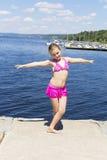 Muchacha linda en el riverbank en traje de baño rosado imagen de archivo libre de regalías