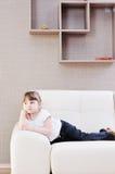 Muchacha linda en el sofá en la azada Foto de archivo libre de regalías