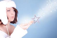 Muchacha linda en el sombrero blanco que sopla una nieve Foto de archivo